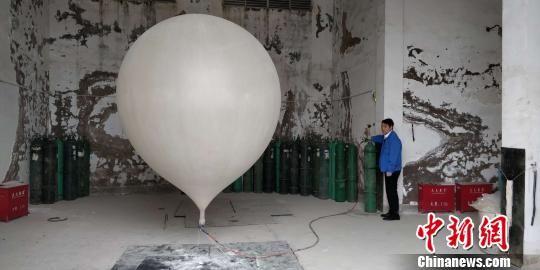 贵阳市高空气象探测站高级工程师闵昌红正在为探空气球灌装氢气 曾实 摄