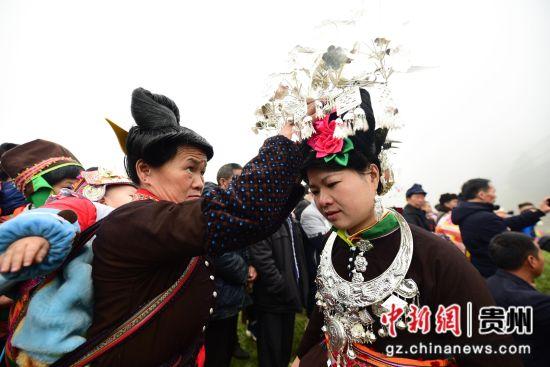图为一名苗族妇女在帮助锦鸡舞舞者整理银饰。 杨武魁 摄