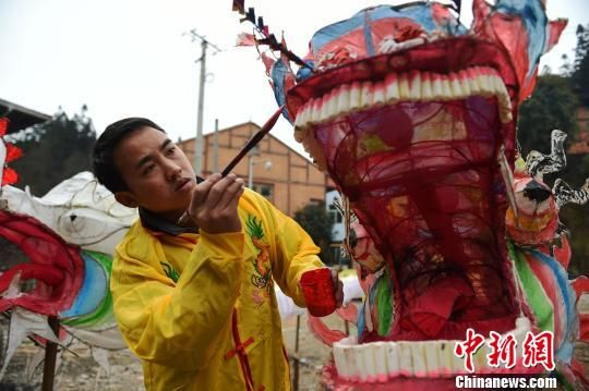 贵州省台江县台拱街道温泉村大德苗寨的村民在给龙头添色。 刘开福 摄