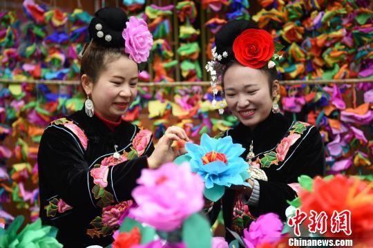 贵州省台江县台拱街道温泉村大德苗寨的村民在整理装饰彩龙的花纸。 冯桂菊 摄