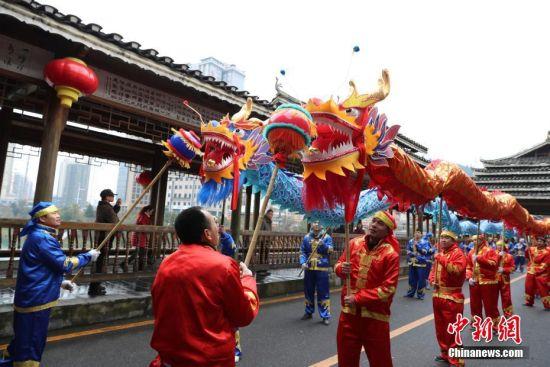 2月19日,民间艺人在贵州省铜仁市玉屏侗族自治县风雨桥上进行舞龙表演,欢庆元宵佳节。中新社发 胡攀学 摄