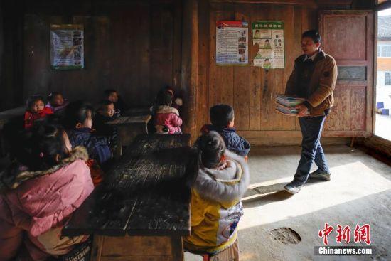 """2月25日,48岁的侗族代课教师潘平忠抱着书本走进教室,开始新学期的第一课。当日,是新学期开学的第一天,在贵州省黔东南苗族侗族自治州榕江县平永镇阶你村�I尧教学点,村里唯一的一名代课老师潘平忠和他的一年级18个学生迎来了新学期的第一课。上世纪90年代初,潘平忠回到自己的家乡当起了一名代课老师,这一干就是28年。由于师资的缺乏让潘平忠不得不教授语文、数学、美术等所有科目,还得为学生们做营养午餐、辅导功课。目前,�I尧教学点硬件设施逐步得到改善。潘平忠说:""""对农村孩子而言,教育极为重要。希望今后有新的老师加入,让孩子能学习更多先进知识文化。""""中新社记者 贺俊怡 摄"""