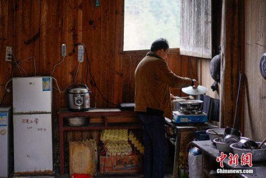 """2月25日,代课教师潘平忠在教学点为学生制作午餐。当日,是新学期开学的第一天,在贵州省黔东南苗族侗族自治州榕江县平永镇阶你村�I尧教学点,村里唯一的一名代课老师潘平忠和他的一年级18个学生迎来了新学期的第一课。上世纪90年代初,潘平忠回到自己的家乡当起了一名代课老师,这一干就是28年。由于师资的缺乏让潘平忠不得不教授语文、数学、美术等所有科目,还得为学生们做营养午餐、辅导功课。目前,�I尧教学点硬件设施逐步得到改善。潘平忠说:""""对农村孩子而言,教育极为重要。希望今后有新的老师加入,让孩子能学习更多先进知识文化。""""中新社记者 贺俊怡 摄"""