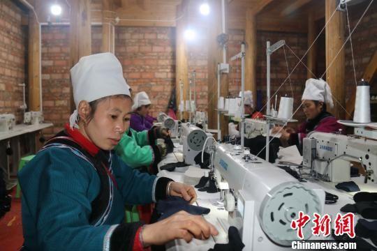 图为水族妇女在缝纫手套里布。 姚源芳 摄