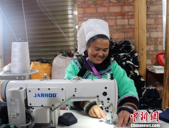图为水族妇女潘老仙在缝纫手套里布。 姚源芳 摄