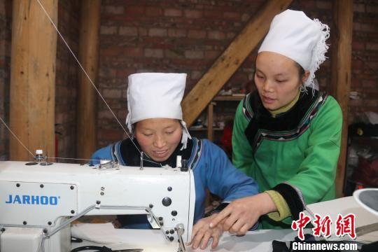 图为水族妇女潘银花(右)正在教授韦老念缝纫技术。 姚源芳 摄