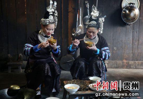 图为石婢四和女儿一起品尝油茶。