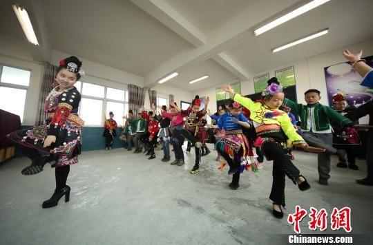 """图为老师在教兴趣班的学生跳""""苗族锦鸡舞""""。 黄晓海 摄"""