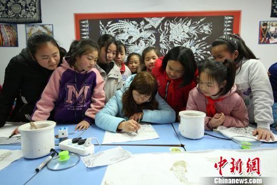 """图为美术老师在给兴趣班的学生示范""""苗族蜡染""""的绘画步骤。 黄晓海 摄"""