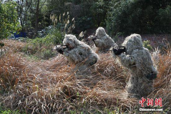 """3月21日,特战队员在进行伪装侦察训练。当日,为期7天的武警贵州省总队贵阳片区特战分队""""魔鬼周""""第4个极限训练日在贵州贵安新区进行。训练旨在全面提高特战分队在艰苦环境和复杂条件下的综合作战能力。中新社记者 瞿宏伦 摄"""