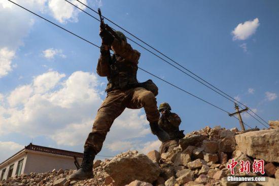 武警贵州总队机动支队特战队员越过路障。中新社记者 瞿宏伦 摄