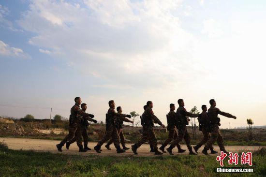 武警贵州总队机动支队特战队员训练完后走回营地。中新社记者 瞿宏伦 摄