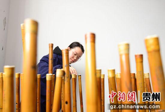 3月23日,在贵州省铜仁市玉屏侗族自治县箫笛生产基地一家企业车间,工人正在检查箫笛上漆情况。