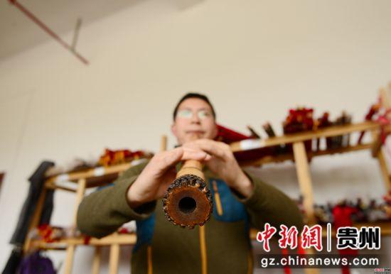 3月23日,在贵州省铜仁市玉屏侗族自治县箫笛生产基地一家企业车间,工人正在检验箫笛音质。
