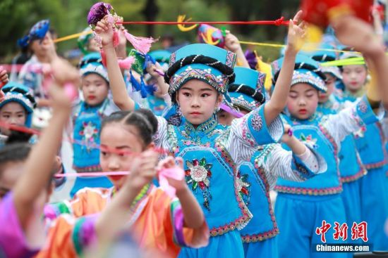 布依族小朋友在巡游中跳糠包舞。中新社记者 贺俊怡 摄