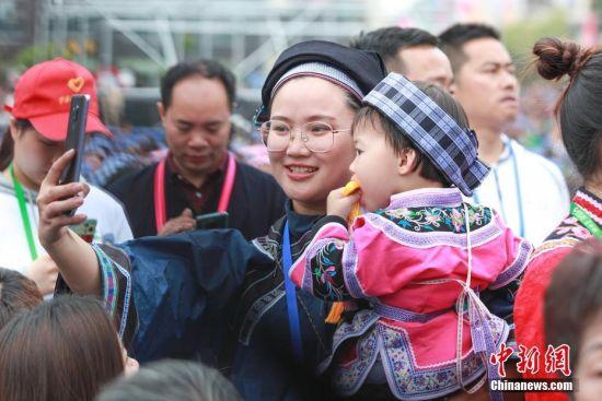 一名布依族女青年与小朋友自拍留念。中新社记者 贺俊怡 摄