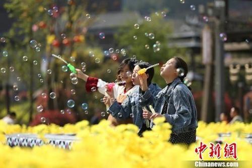4月5日,贵州丹寨万达小镇景区,几名女孩在花海中吹泡泡。黄晓海 摄