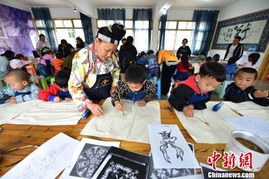 图为幼儿园小朋友在蜡染画师的指导下学画蜡画。 杨武魁 摄