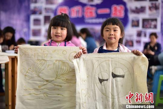 图为幼儿园小朋友在展示她们画的蜡画。 杨武魁 摄