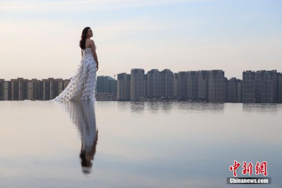 """4月11日,一名女子在""""天空之镜""""景点拍摄写真。当日,贵州贵阳市泉湖公园内的""""天空之镜""""景点吸引了不少游客前来拍照游玩。该景点位于公园山顶,是一个直径8米左右的圆形水池,宛如一面巨大的镜子,倒映出天空、白云、高楼等景色。中新社记者 瞿宏伦 摄"""