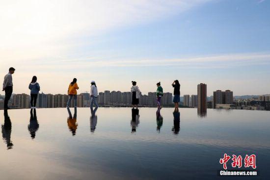 """4月11日,游客们在""""天空之镜""""景点游玩。当日,贵州贵阳市泉湖公园内的""""天空之镜""""景点吸引了不少游客前来拍照游玩。该景点位于公园山顶,是一个直径8米左右的圆形水池,宛如一面巨大的镜子,倒映出天空、白云、高楼等景色。中新社记者 瞿宏伦 摄"""