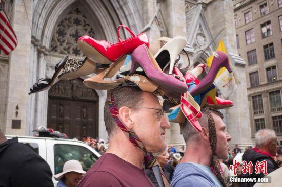 当地时间4月21日,两名男士头顶高跟鞋花帽在纽约参加复活节花帽游行。当日是西方传统节日复活节,人们头戴精心制作的花帽,在纽约第五大道参加一年一度的复活节游行。 中新社记者 廖攀 摄
