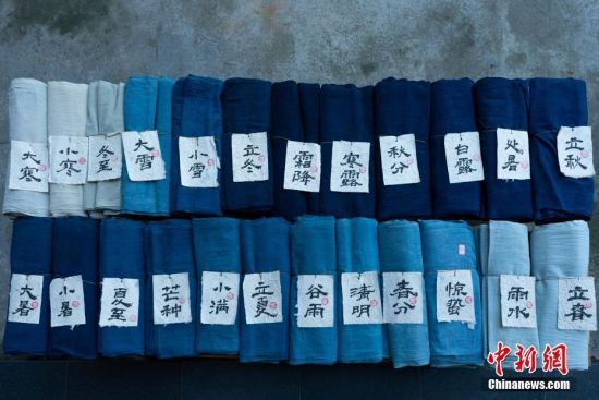 """蓝染是中国一种古老的印染工艺,已有上千年历史。在许多人眼里,蓝染只有一种颜色,而在贵州省榕江县,一位名叫赖蕾的侗族织娘却能染出二十四种色调,让蓝染有了第一份色谱――""""黔蓝""""。今年44岁的侗族织娘赖蕾,在高中毕业后考取了云南艺术学院油画专业。毕业后,她做过乡村教师、机关职员,最后选择了侗族传统手工技艺――织布、染布。赖蕾于2015年7月成立贵州娘美布彩印染坊,改良传统织布机和创新侗族传统染布技艺,融入现代时尚元素,生产布匹、服装、女式包、床上用品、茶席等文创产品,远销美国、法国及北京、上海、广州等地,年产值超过1000万元人民币,并带动榕江、从江等周边地区上千名妇女就业。赖蕾说,传统侗族人生活场景比较单一,与之相匹配的土布面料也没有几款,而且都是单一的一种蓝色调,纺织作坊开久了,就萌发了创新的心思,想要调制出一份蓝染色谱。在长时间摸索中,赖蕾发现在不同的温度和气候条件下所染出蓝色都会有所不同,于是就分别在春分、清明、谷雨、立夏、小满等二十四节气时将布染出了24种不同的蓝。2017年,""""二十四节气染布""""因具有较高的艺术与审美价值被中国民族博物馆收藏,由此衍生出的文创产品也得到了很多商家的青睐。中新社记者 贺俊怡 摄"""