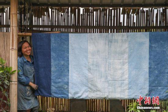 """蓝染是中国一种古老的印染工艺,已有上千年历史。在许多人眼里,蓝染只有一种颜色,而在贵州省榕江县,一位名叫赖蕾的侗族织娘却能染出二十四种色调,让蓝染有了第一份色谱――""""黔蓝""""。今年44岁的侗族织娘赖蕾,在高中毕业后考取了云南艺术学院油画专业。毕业后,她做过乡村教师、机关职员,最后选择了侗族传统手工技艺――织布、染布。赖蕾于2015年7月成立贵州娘美布彩印染坊,改良传统织布机和创新侗族传统染布技艺,融入现代时尚元素,生产布匹、服装、女式包、床上用品、茶席等文创产品,远销美国、法国及北京、上海、广州等地,年产值超过1000万元人民币,并带动榕江、从江等周边地区上千名妇女就业。赖蕾说,传统侗族人生活场景比较单一,与之相匹配的土布面料也没有几款,而且都是单一的一种蓝色调,纺织作坊开久了,就萌发了创新的心思,想要调制出一份蓝染色谱。在长时间摸索中,赖蕾发现在不同的温度和气候条件下所染出蓝色都会有所不同,于是就分别在春分、清明、谷雨、立夏、小满等二十四节气时将布染出了24种不同的蓝。2017年,""""二十四节气染布""""因具有较高的艺术与审美价值被中国民族博物馆收藏,由此衍生出的文创产品也得到了很多商家的青睐。图为在染坊晾晒区,赖蕾展示一款苏州客商订制的不同蓝色组成的布艺成品。中新社记者 贺俊怡 摄"""