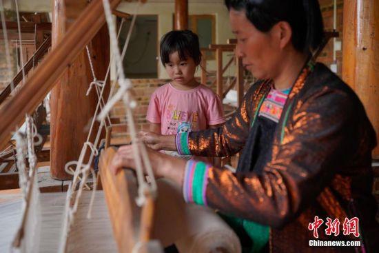 """蓝染是中国一种古老的印染工艺,已有上千年历史。在许多人眼里,蓝染只有一种颜色,而在贵州省榕江县,一位名叫赖蕾的侗族织娘却能染出二十四种色调,让蓝染有了第一份色谱――""""黔蓝""""。今年44岁的侗族织娘赖蕾,在高中毕业后考取了云南艺术学院油画专业。毕业后,她做过乡村教师、机关职员,最后选择了侗族传统手工技艺――织布、染布。赖蕾于2015年7月成立贵州娘美布彩印染坊,改良传统织布机和创新侗族传统染布技艺,融入现代时尚元素,生产布匹、服装、女式包、床上用品、茶席等文创产品,远销美国、法国及北京、上海、广州等地,年产值超过1000万元人民币,并带动榕江、从江等周边地区上千名妇女就业。赖蕾说,传统侗族人生活场景比较单一,与之相匹配的土布面料也没有几款,而且都是单一的一种蓝色调,纺织作坊开久了,就萌发了创新的心思,想要调制出一份蓝染色谱。在长时间摸索中,赖蕾发现在不同的温度和气候条件下所染出蓝色都会有所不同,于是就分别在春分、清明、谷雨、立夏、小满等二十四节气时将布染出了24种不同的蓝。2017年,""""二十四节气染布""""因具有较高的艺术与审美价值被中国民族博物馆收藏,由此衍生出的文创产品也得到了很多商家的青睐。图为来自各个村寨和周边县的侗族妇女在赖蕾的染坊里,既解决了就业的问题,又能照顾到家里的老人和孩子。中新社记者 贺俊怡 摄"""