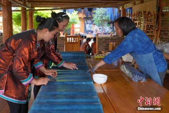 """蓝染是中国一种古老的印染工艺,已有上千年历史。在许多人眼里,蓝染只有一种颜色,而在贵州省榕江县,一位名叫赖蕾的侗族织娘却能染出二十四种色调,让蓝染有了第一份色谱——""""黔蓝""""。今年44岁的侗族织娘赖蕾,在高中毕业后考取了云南艺术学院油画专业。毕业后,她做过乡村教师、机关职员,最后选择了侗族传统手工技艺——织布、染布。赖蕾于2015年7月成立贵州娘美布彩印染坊,改良传统织布机和创新侗族传统染布技艺,融入现代时尚元素,生产布匹、服装、女式包、床上用品、茶席等文创产品,远销美国、法国及北京、上海、广州等地,年产值超过1000万元人民币,并带动榕江、从江等周边地区上千名妇女就业。赖蕾说,传统侗族人生活场景比较单一,与之相匹配的土布面料也没有几款,而且都是单一的一种蓝色调,纺织作坊开久了,就萌发了创新的心思,想要调制出一份蓝染色谱。在长时间摸索中,赖蕾发现在不同的温度和气候条件下所染出蓝色都会有所不同,于是就分别在春分、清明、谷雨、立夏、小满等二十四节气时将布染出了24种不同的蓝。2017年,""""二十四节气染布""""因具有较高的艺术与审美价值被中国民族博物馆收藏,由此衍生出的文创产品也得到了很多商家的青睐。图为赖蕾在指导两位织娘对染蓝的侗布""""上鸡蛋清""""。中新社记者 贺俊怡 摄"""