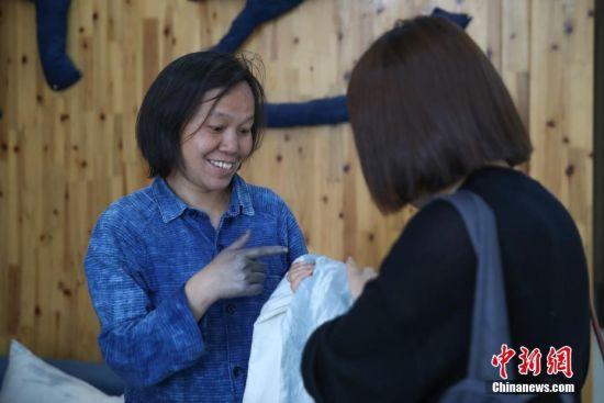 """蓝染是中国一种古老的印染工艺,已有上千年历史。在许多人眼里,蓝染只有一种颜色,而在贵州省榕江县,一位名叫赖蕾的侗族织娘却能染出二十四种色调,让蓝染有了第一份色谱――""""黔蓝""""。今年44岁的侗族织娘赖蕾,在高中毕业后考取了云南艺术学院油画专业。毕业后,她做过乡村教师、机关职员,最后选择了侗族传统手工技艺――织布、染布。赖蕾于2015年7月成立贵州娘美布彩印染坊,改良传统织布机和创新侗族传统染布技艺,融入现代时尚元素,生产布匹、服装、女式包、床上用品、茶席等文创产品,远销美国、法国及北京、上海、广州等地,年产值超过1000万元人民币,并带动榕江、从江等周边地区上千名妇女就业。赖蕾说,传统侗族人生活场景比较单一,与之相匹配的土布面料也没有几款,而且都是单一的一种蓝色调,纺织作坊开久了,就萌发了创新的心思,想要调制出一份蓝染色谱。在长时间摸索中,赖蕾发现在不同的温度和气候条件下所染出蓝色都会有所不同,于是就分别在春分、清明、谷雨、立夏、小满等二十四节气时将布染出了24种不同的蓝。2017年,""""二十四节气染布""""因具有较高的艺术与审美价值被中国民族博物馆收藏,由此衍生出的文创产品也得到了很多商家的青睐。图为在工作室内,赖蕾向苏州来的客商推荐蓝色的布艺产品。中新社记者 贺俊怡 摄"""