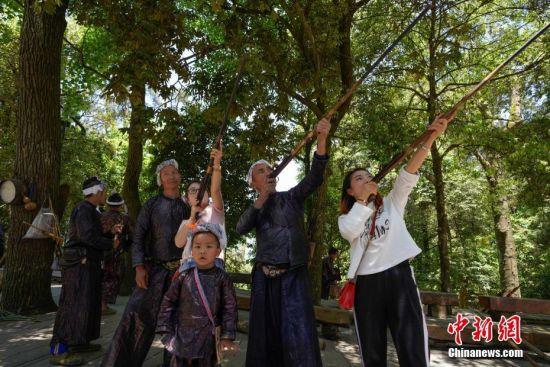 """5月1日,两名女游客手持火药枪合影留念。当日,五一国际劳动节假期首日,众多游客来到贵州省从江县丙妹镇岜沙村,感受苗寨民俗风情。岜沙是一个崇尚自然、以树为神的苗家村寨,被誉为""""世界最后一个枪手部落""""。 中新社记者 贺俊怡 摄"""