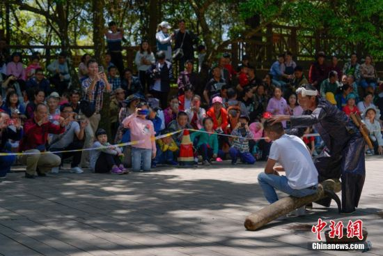 """5月1日,一名游客体验镰刀剃头引围观。当日,五一国际劳动节假期首日,众多游客来到贵州省从江县丙妹镇岜沙村,感受苗寨民俗风情。岜沙是一个崇尚自然、以树为神的苗家村寨,被誉为""""世界最后一个枪手部落""""。 中新社记者 贺俊怡 摄"""