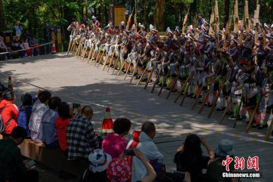 """5月1日,游客观看苗族芦笙舞表演。当日,五一国际劳动节假期首日,众多游客来到贵州省从江县丙妹镇岜沙村,感受苗寨民俗风情。岜沙是一个崇尚自然、以树为神的苗家村寨,被誉为""""世界最后一个枪手部落""""。 中新社记者 贺俊怡 摄"""