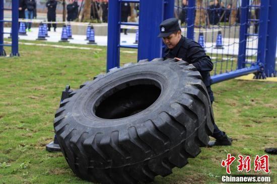 特警队员进行翻滚轮胎训练。