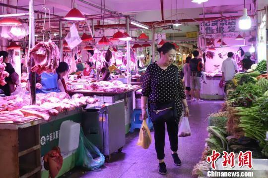 林素珍在菜市场购买食材。瞿宏伦 摄