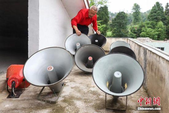 """5月18日,杨绍友在展示使用过的部分喇叭。今年70岁的杨绍友是贵州省铜仁市玉屏侗族自治县田坪镇人。1964年,因为喜爱广播事业,杨绍友开始攒钱买大喇叭在村里做""""小广播"""",开启了自己的""""乡村主播""""之路,55年来,他已经累计购买了30余只大喇叭。中新社记者 瞿宏伦 摄"""