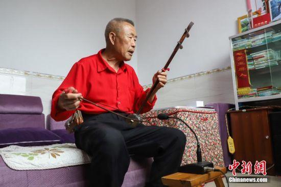 杨绍友在整理使用过的话筒。中新社记者 瞿宏伦 摄