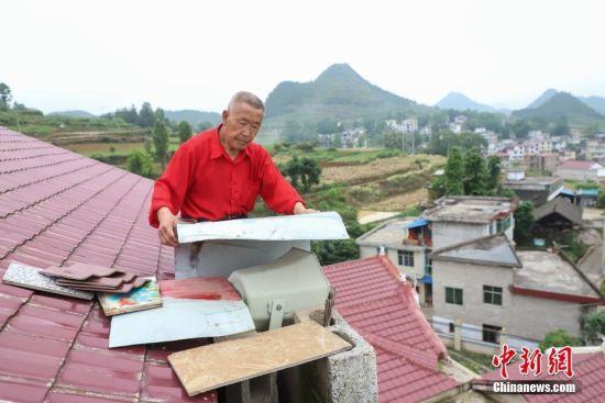 杨绍友在屋顶用铁皮遮盖喇叭。中新社记者 瞿宏伦 摄