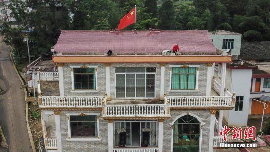 航拍杨绍友在屋顶整理喇叭。中新社记者 瞿宏伦 摄