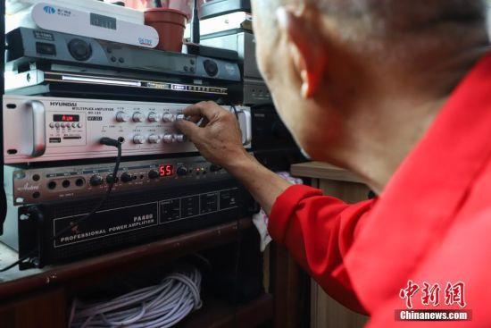 """杨绍友在通过设备调节播出音量的大小。杨绍友说:""""如今村里人都忙着脱贫致富,我上了年纪,能干的事情不多,就用广播尽一份力,为乡亲们助威。""""中新社记者 瞿宏伦 摄"""