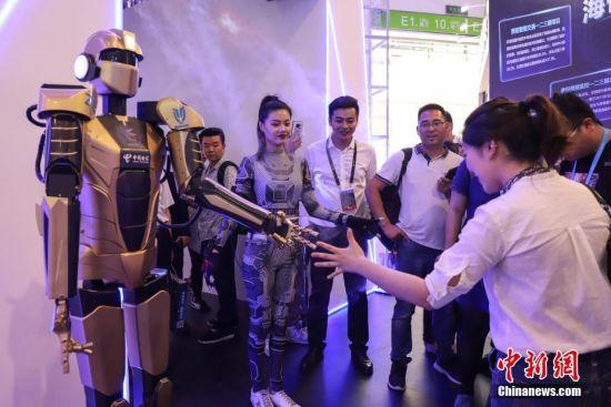 """5月27日,一位参观者在和5G远程控制机器人""""猜拳""""。5月26日至29日,以""""创新发展,数说未来""""为主题的2019中国国际大数据产业博览会在贵阳启幕,吸引市民观展。中新社记者 瞿宏伦 摄"""
