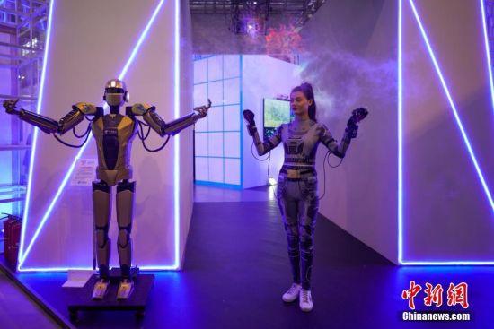 """5月27日,参展商在用5G设备远程操控机器人。5月26日至29日,以""""创新发展,数说未来""""为主题的2019中国国际大数据产业博览会在贵阳启幕,吸引民众观展。中新社记者 贺俊怡 摄"""