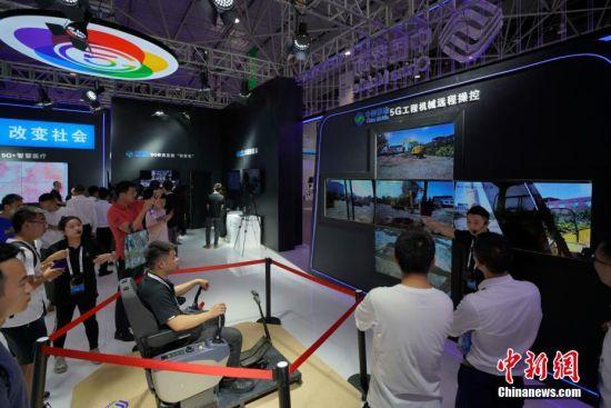 """5月27日,参观者在观看中国移动5G工程机械远程操控挖掘机演示。5月26日至29日,以""""创新发展,数说未来""""为主题的2019中国国际大数据产业博览会在贵阳启幕,吸引民众观展。中新社记者 贺俊怡 摄"""
