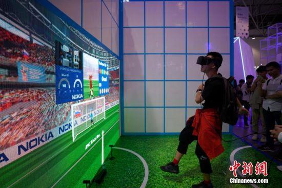 """5月27日,一位参观者在体验中国电信5G运动馆足球项目。5月26日至29日,以""""创新发展,数说未来""""为主题的2019中国国际大数据产业博览会在贵阳启幕,吸引民众观展。中新社记者 贺俊怡 摄"""