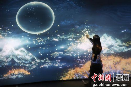 5月28日,一位参观者在《觅象数谷》作品前触摸体感屏幕。