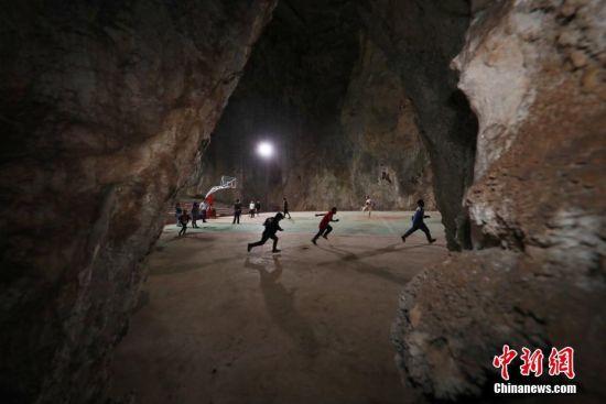 近日,贵州省纳雍县猪场乡新春村村民在溶洞球场里练习篮球。
