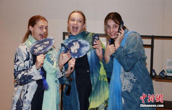 """6月19日,悉尼中学生到中国文化中心体验""""魅力贵州""""。正在悉尼中国文化中心举办的""""2019年澳大利亚中国旅游文化周 --- 多彩文化·魅力贵州""""主题展,吸引当地市民领略贵州人文艺术和旅游文化的独特魅力。图为女学生体验贵州蜡染服饰。 中新社记者 陶社兰 摄"""