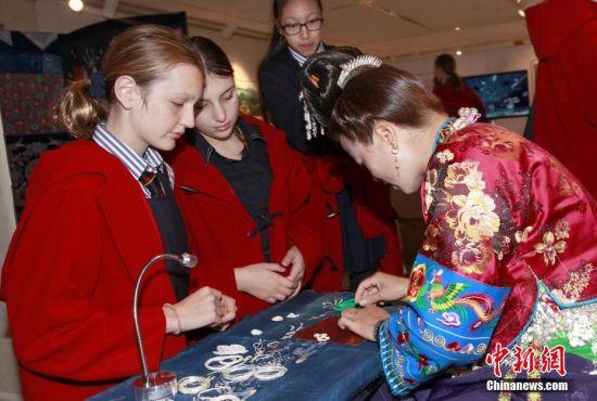 """6月19日,悉尼中学生到中国文化中心体验""""魅力贵州""""。正在悉尼中国文化中心举办的""""2019年澳大利亚中国旅游文化周 --- 多彩文化・魅力贵州""""主题展,吸引当地市民领略贵州人文艺术和旅游文化的独特魅力。图为女学生体验贵州蜡染服饰。 中新社记者 陶社兰 摄"""