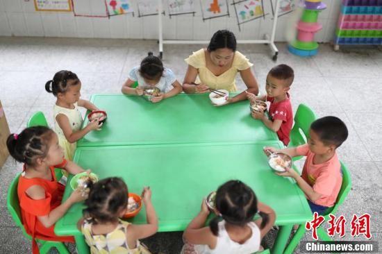 贵州玉屏,邹金香与学生在一起吃午餐。